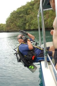 diver making boat entry into water in palau with bentprop