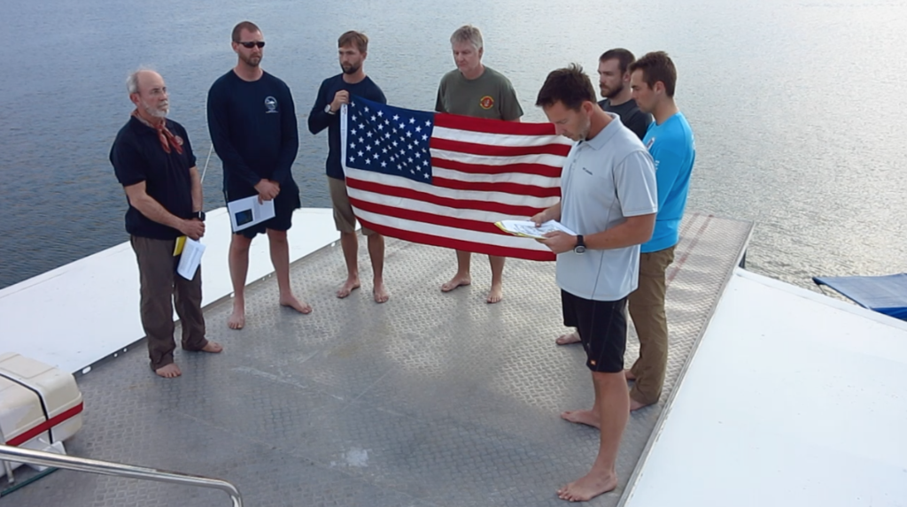 Project Recover team members conduct a flag ceremony to honor the missing service members still associated with the discovered B-25