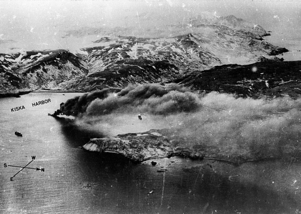 The 474-feet long Japanese transport ship Nisan Maru sinking in the middle of Kiska Harbor after it was stuck by bombs dropped by the US 11th Air force on 18 June 1942. Two other Japanese ships are visible in the harbor nearby.