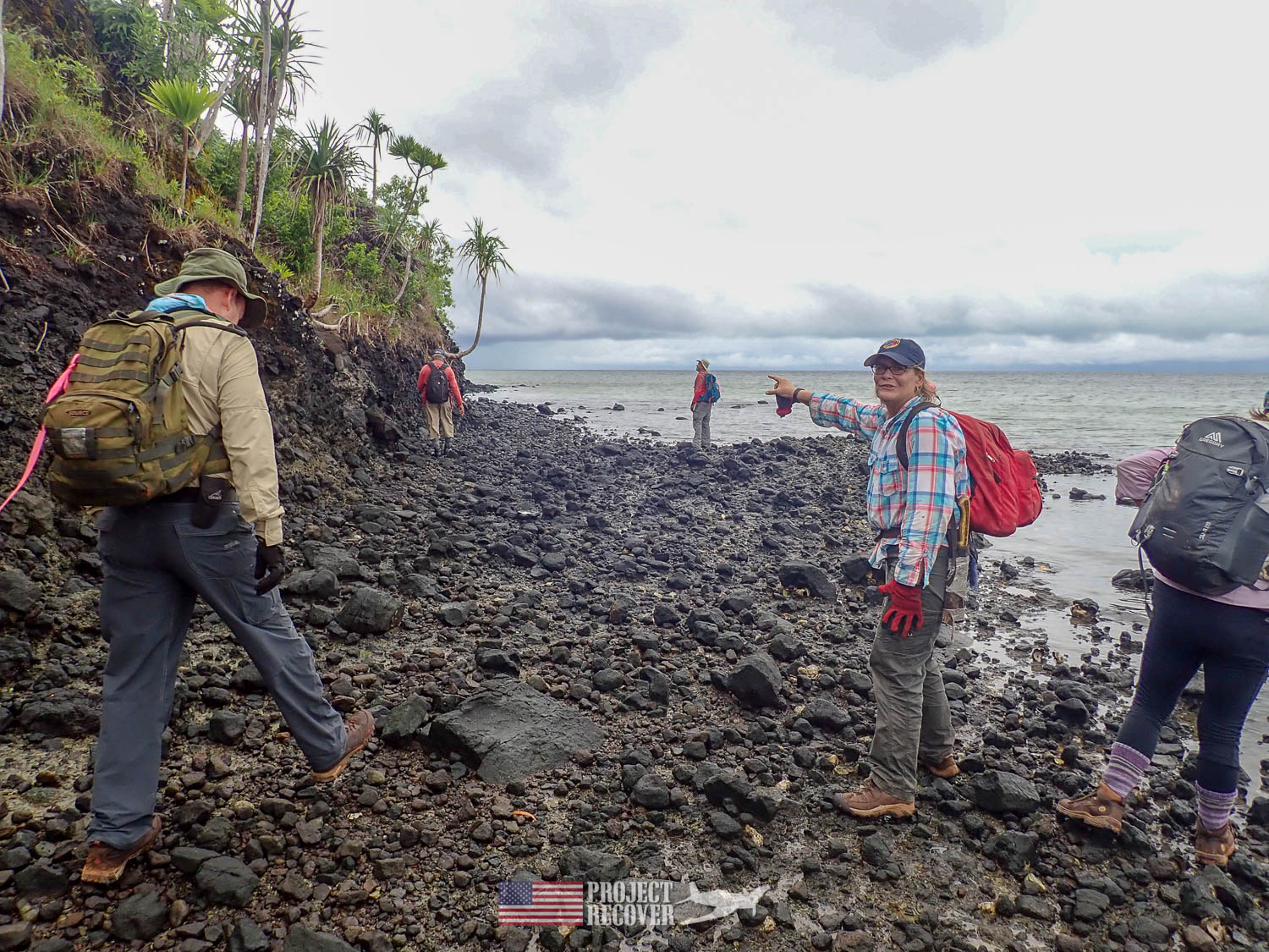 PR team walks through rocky beach.Execution of WWII POWs and Innocents in Palau - Project Recover is committed to bringing the MIA home. Photos by Harry Parker Photography.com