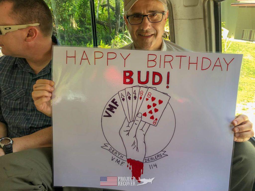 Glenn Frano holds sign wishing Happy Birthday to Glenn 'Bud' Daniel, WWII Corsair pilot who flew during Battle of Peleliu.