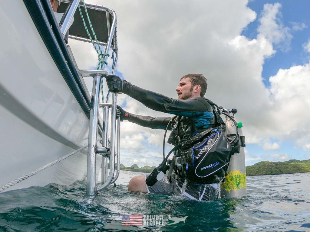 Adam Gray (MIA Family) climbs out of the water after wreck dive in Palau. Photo by Harry Parker Photography.