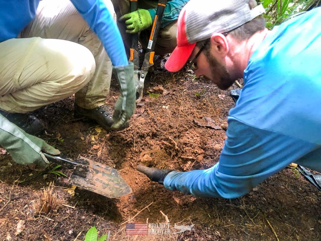 Adam Gray helps with a test pit on a metal detector find in the middle of the Palauan jungle. Our team digs under the supervision of team archaeologist, Jolie Liston, Ph.D. Every artifact is carefully documented. Photo: Harry Parker Photography