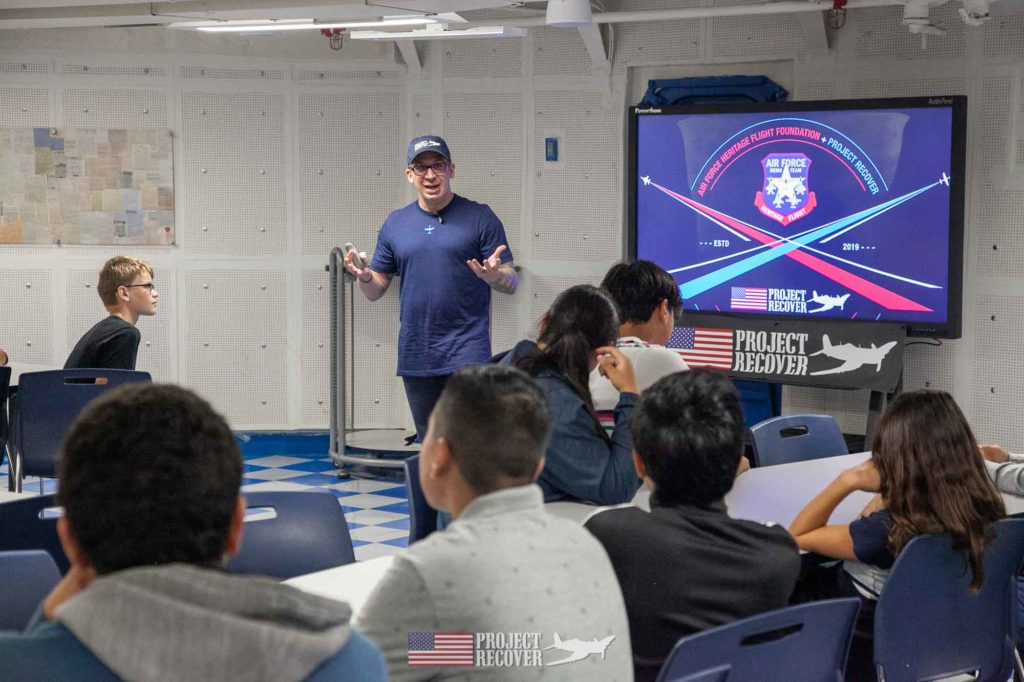 teacher leading students aboard USS Midway
