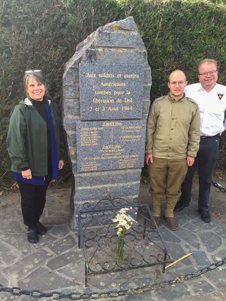 Barbara Daggett stands next monument in Dol-de-Bretagne in honor of men ambushed and killed at that site in WWII. Barbara's grandfather, Capt. Norman S. Ives, was one of them.
