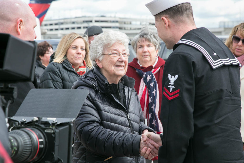Joan Stough, sister of AOM2c Ora H. Sharninghouse shaking hands with navy officer